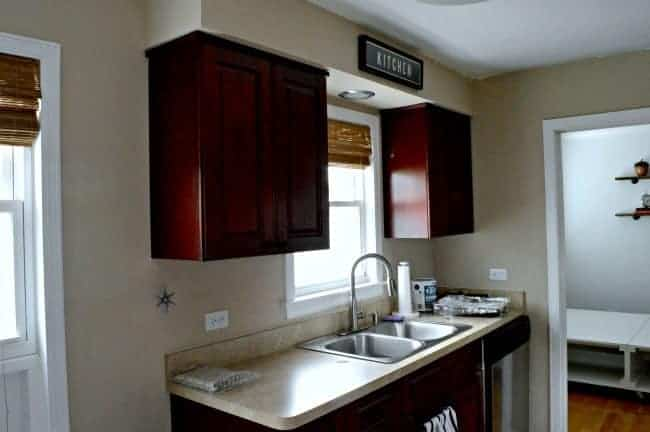 cherry kitchen cabinets and laminate countertop with window over kitchen sink