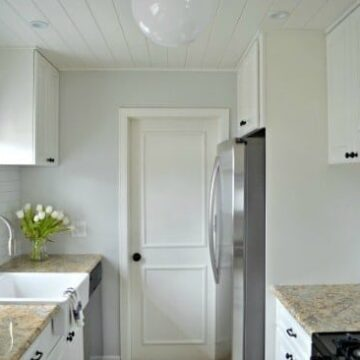 A white kitchen with a sink and a window