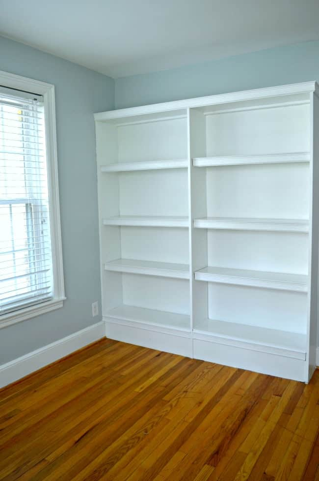 empty white bookcase in guest bedroom painted light blue