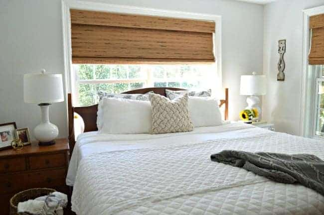 small master bedroom with woven shades and white blanket on bed