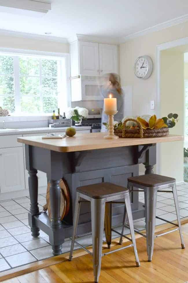 kitchen island painted gray with candle and woven tray on top of butcher block