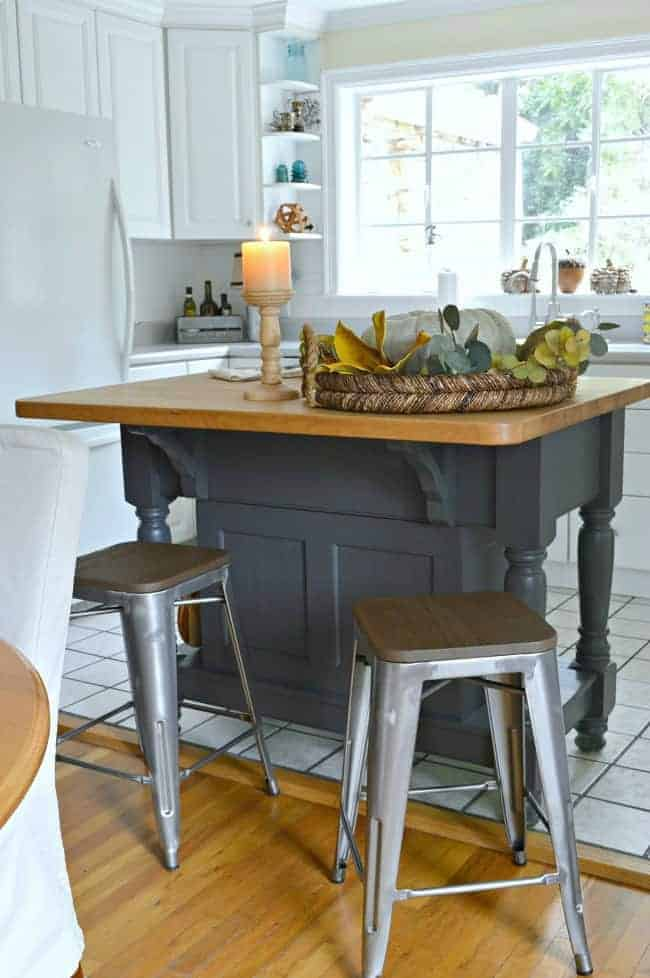 painted kitchen island with a woven tray on top and metal and wood stools