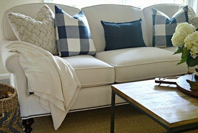 new white couch in living room with navy checked and knitted pillows
