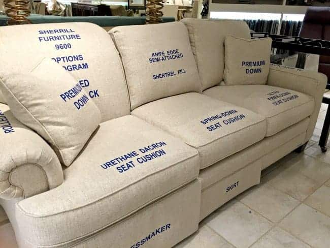 a couch display in a furniture store with labeled seat cushions