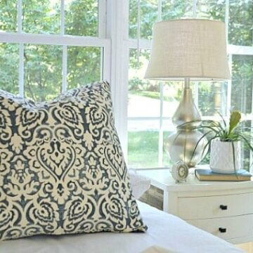 gold painted lamp on nightstand with potted plant in guest bedroom