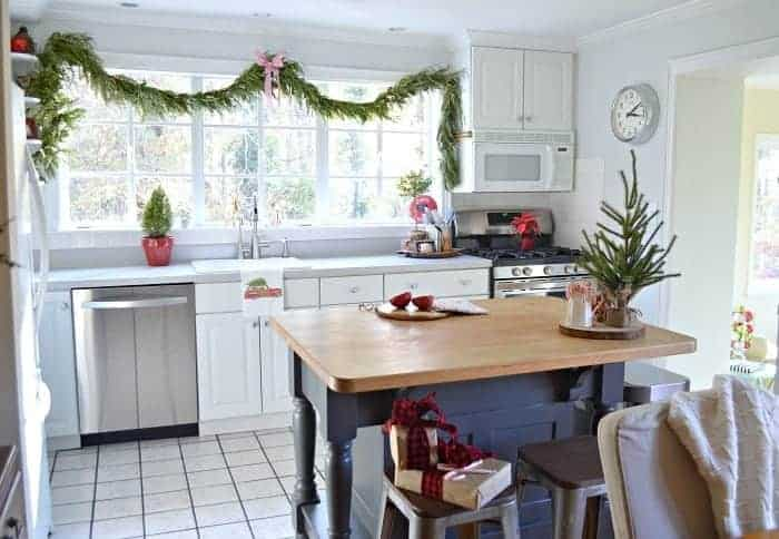 The kitchen in our rustic and simple cozy Christmas cottage decorated in red with touches of gold. www.chafieldcourt.com