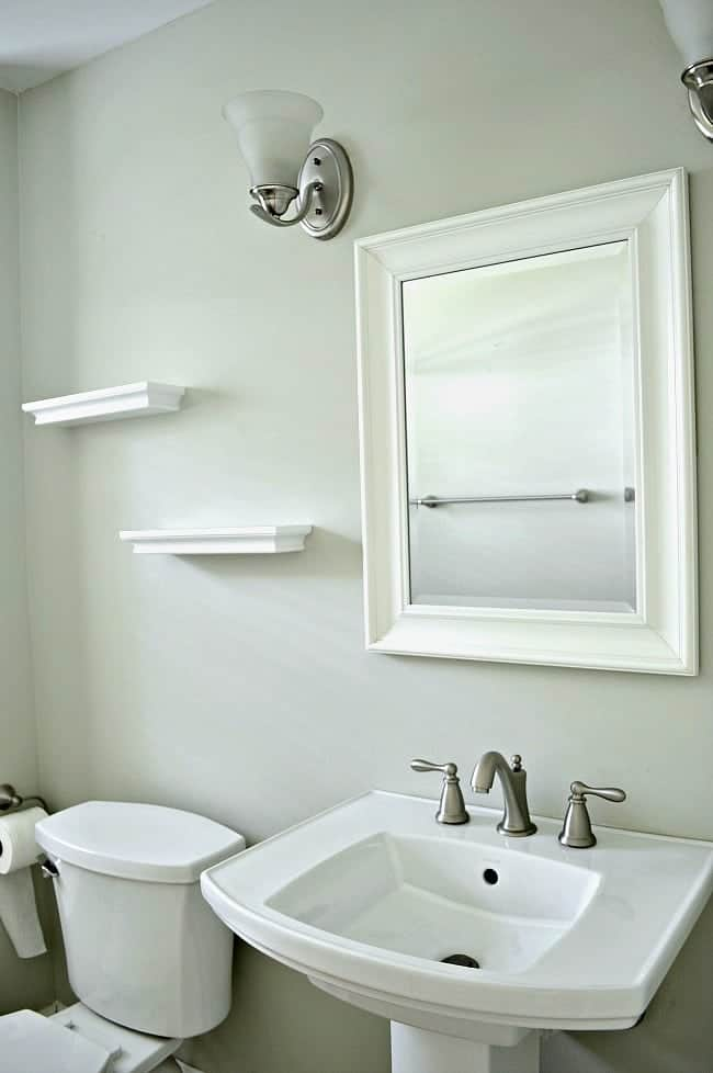 small bathroom sink, mirror and empty shelves hanging on wall