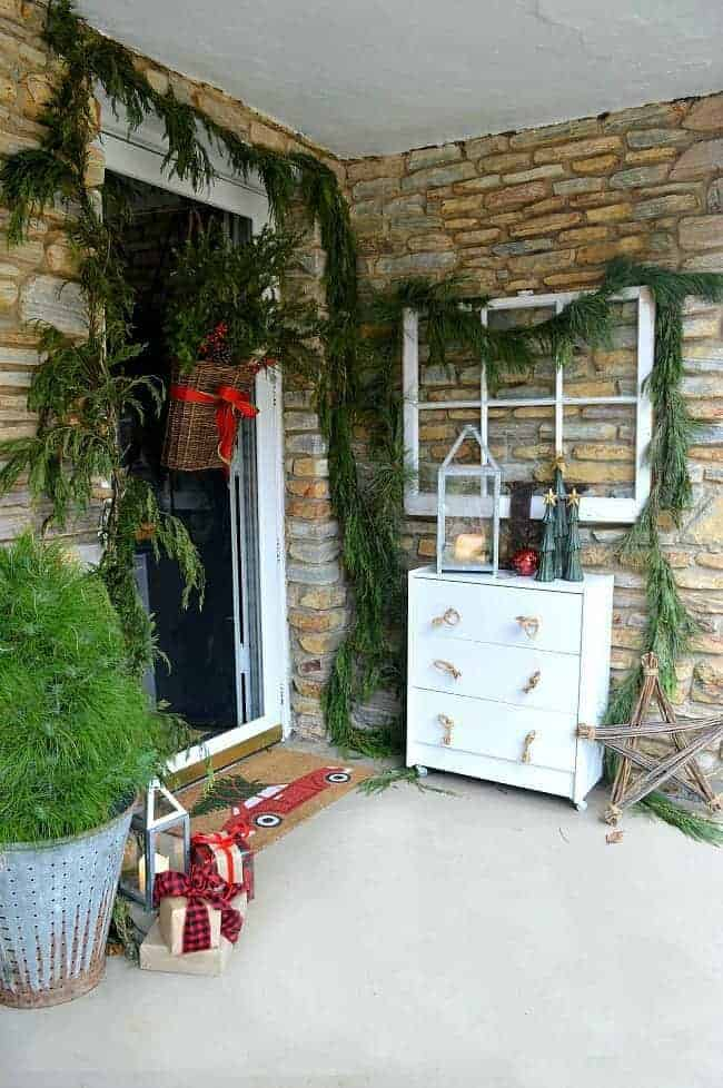 Decorating ideas for a cozy Christmas front porch using fresh garland, lanterns, candles and a few rustic touches. www.chatfieldcourt.com