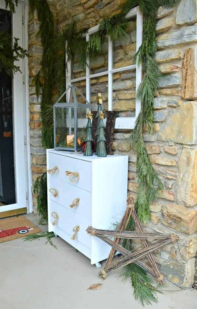 Decorating ideas for a cozy Christmas porch using fresh garland, lanterns, candles and a few rustic touches. www.chatfieldcourt.com