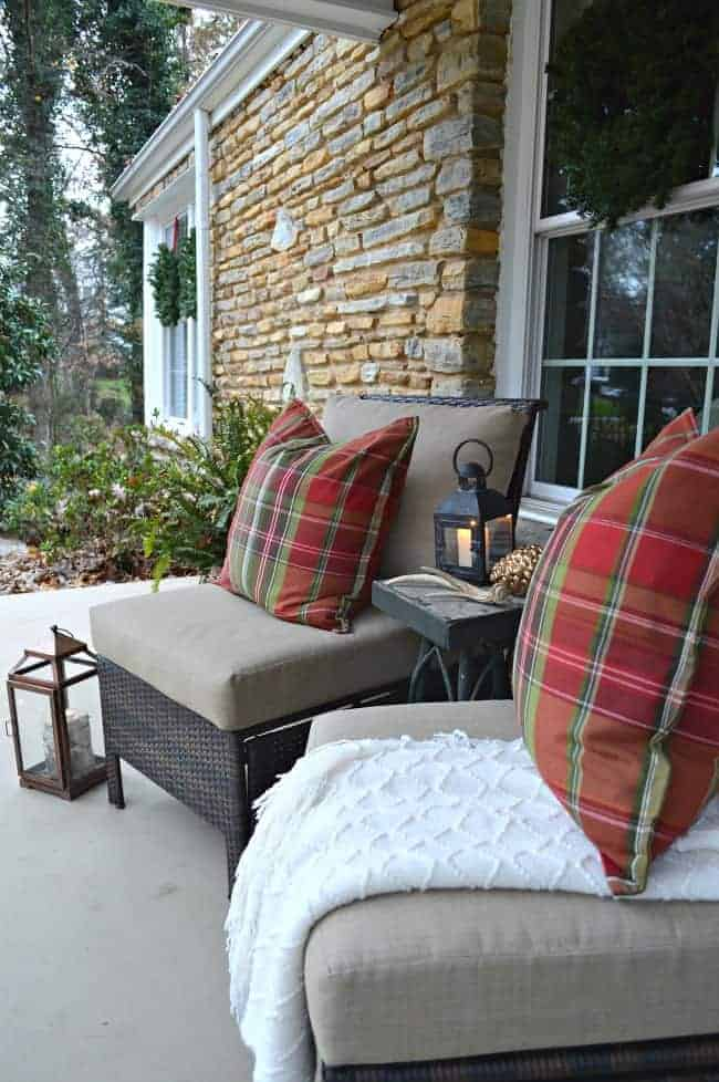 Decorating ideas to create a cozy Christmas porch using fresh garland, candles and a few rustic touches. www.chatfieldcourt.com