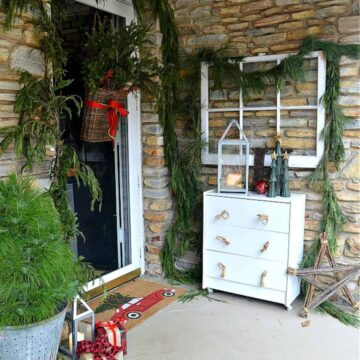 cottage Christmas front porch with greenery around a front door