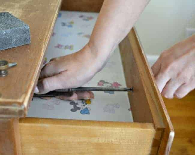removing hardware in top dresser drawer with a screwdriver