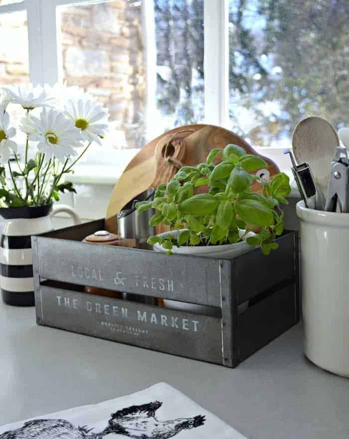 small metal bin with basil plant and wood cutting boards used for cheap kitchen organization