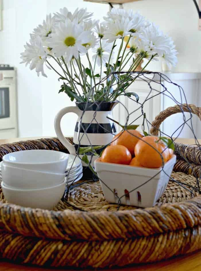 woven tray with white dishes, container of oranges and pitcher of daisies