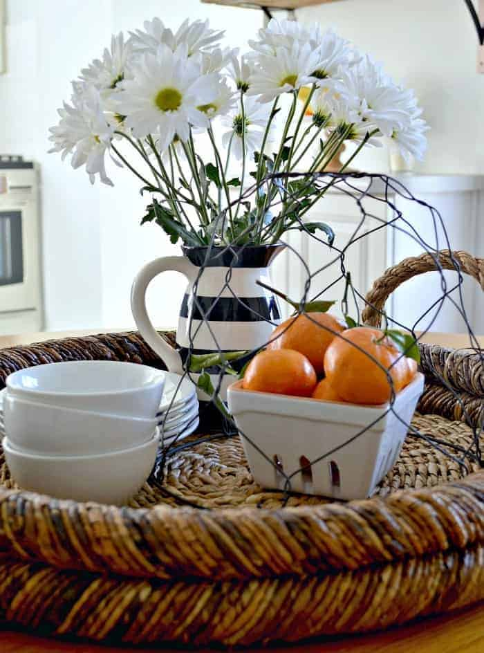 round woven tray with vase of daisies, a bowl of oranges and small white bowls