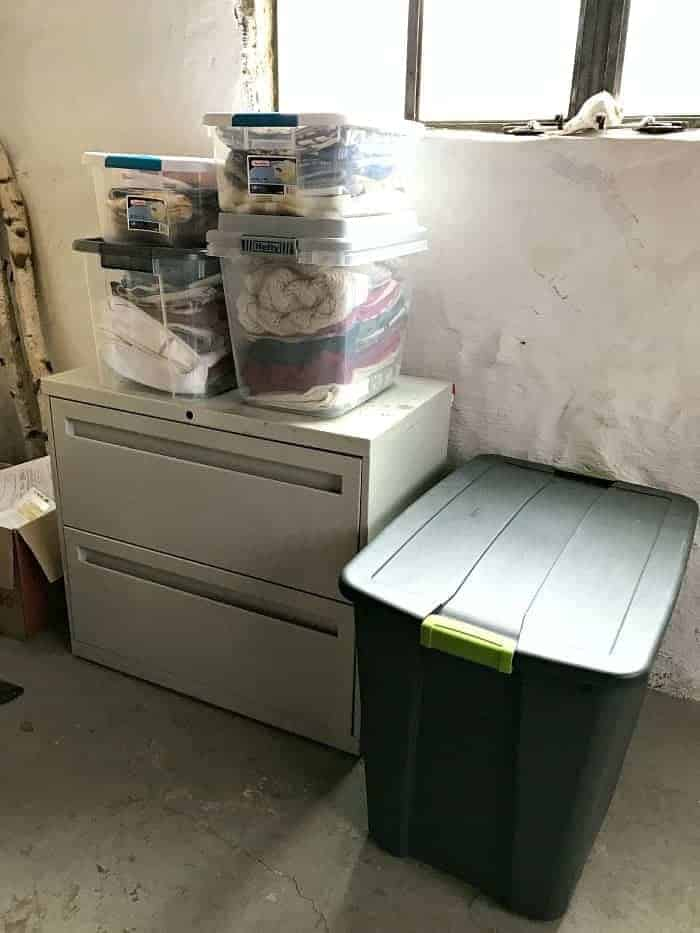 bins of throw pillow covers on file cabinet in basement