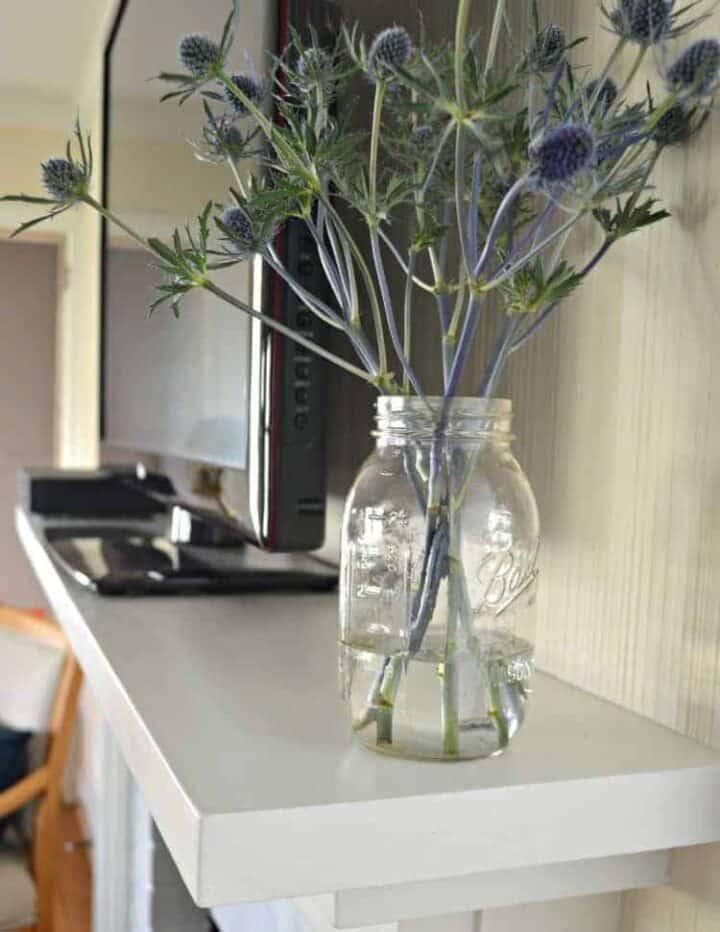 jar of flowers on fireplace mantel
