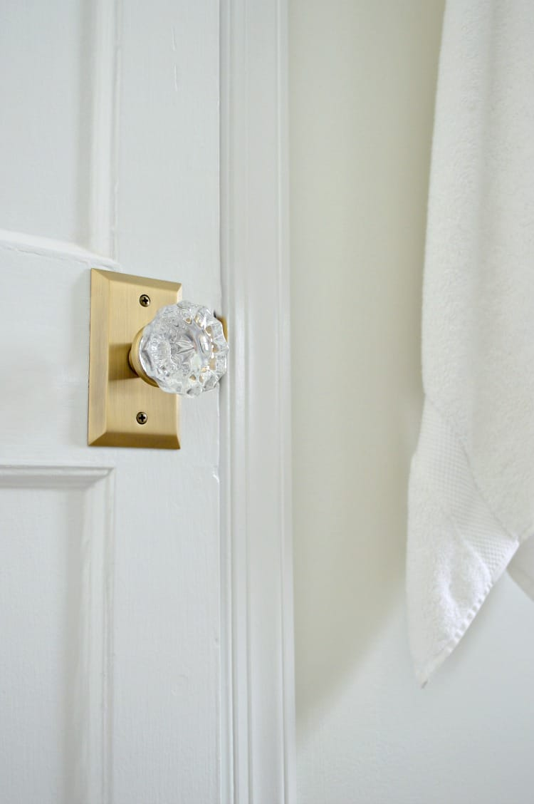 Updating a closet door in a stone cottage bathroom with some elbow grease, paint and beautiful new glass door knobs. A quick and easy DIY to add vintage charm to your home. | Chatfield Court