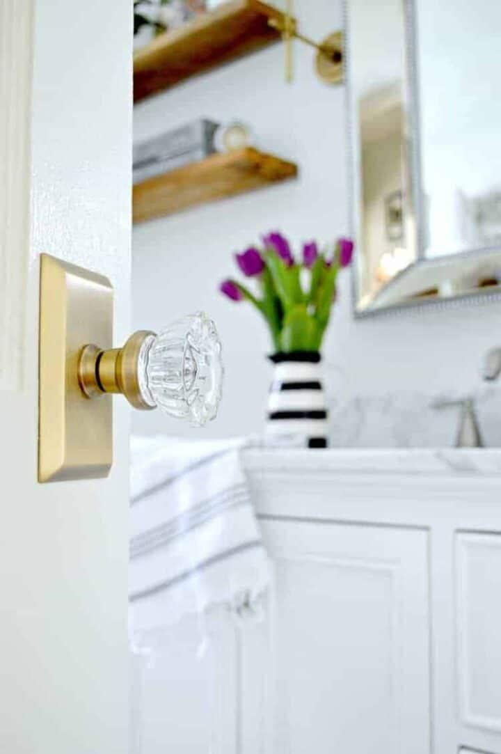 glass door knob on bathroom door with a peek in bathroom