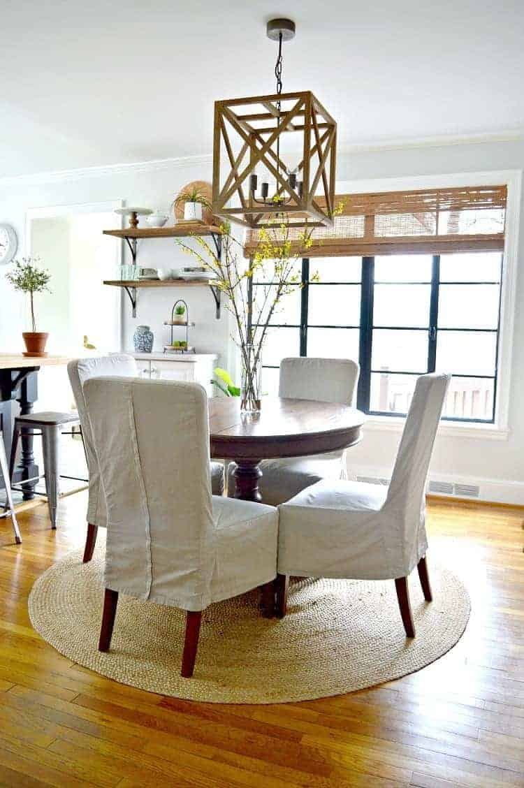 small dining room makeover with round wood table and 4 chairs on jute rug