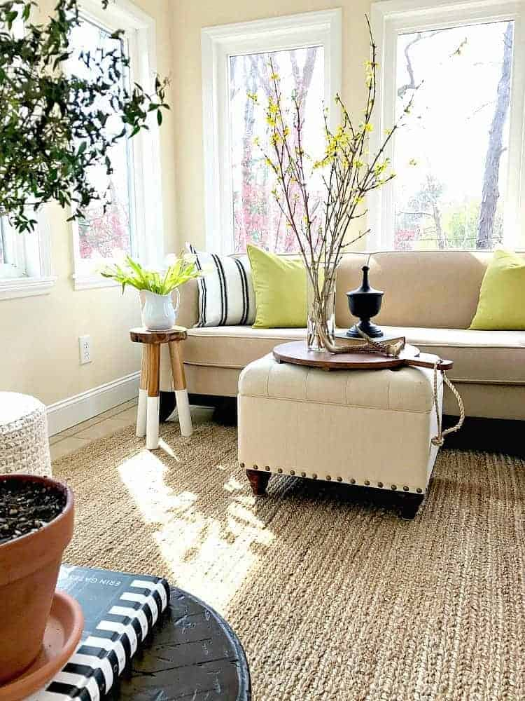 green pillows on beige sofa in sunroom