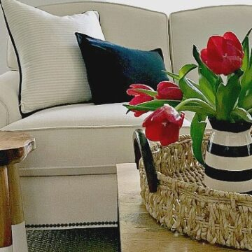 A living room filled with furniture and vase of flowers on a table