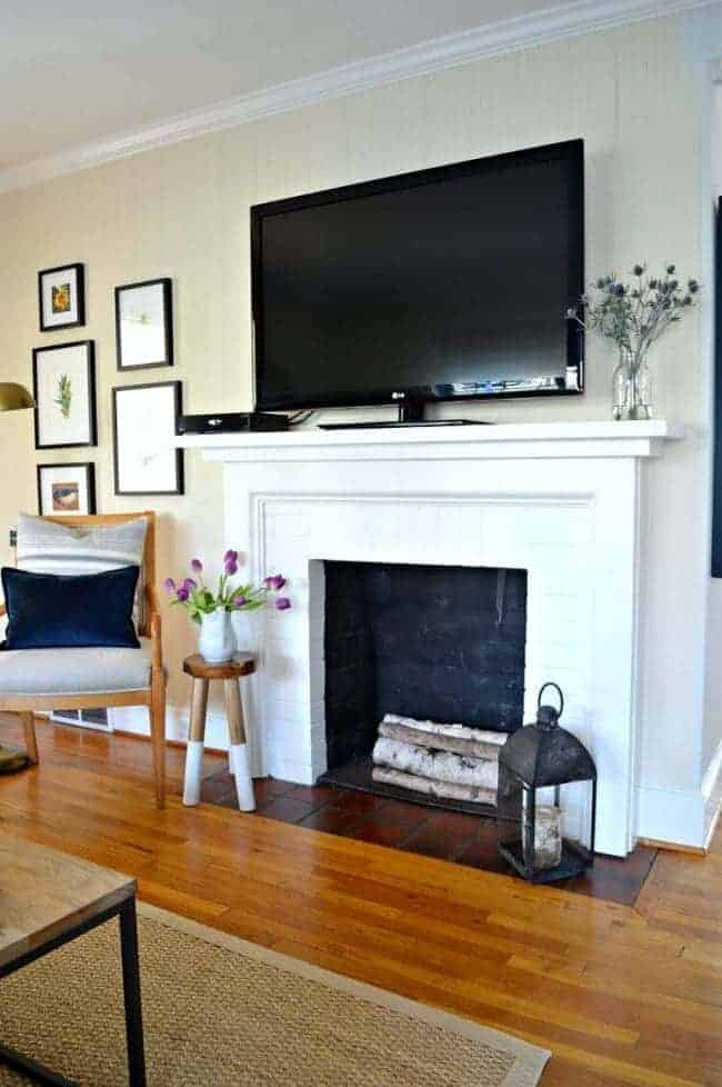 the best white paint colors and a white brick fireplace with large tv on mantle