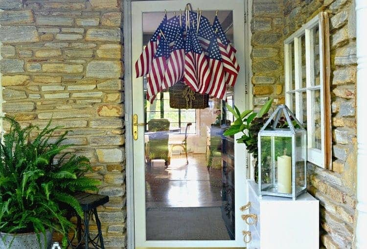 Add a bit of red, white and blue to your front door with this quick and easy American flag display using a hanging basket, floral foam and flags.
