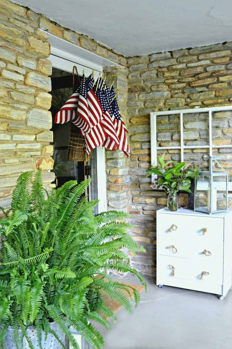 American flag display hanging on a front door of a stone house