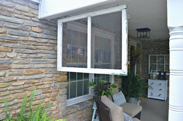 Finding new uses for an old window screen, like hanging it up and using it as a divider on a front porch.