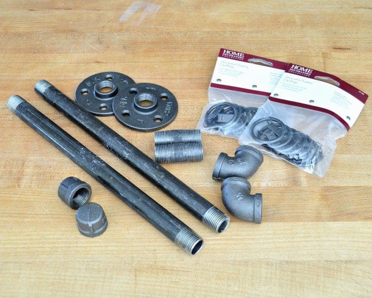 The supplies needed to make DIY custom curtain rods, black pipe and curtain clips