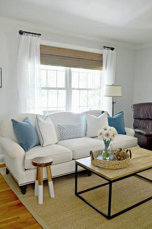 white sofa with blue and white pillows on it and wood and iron coffee table