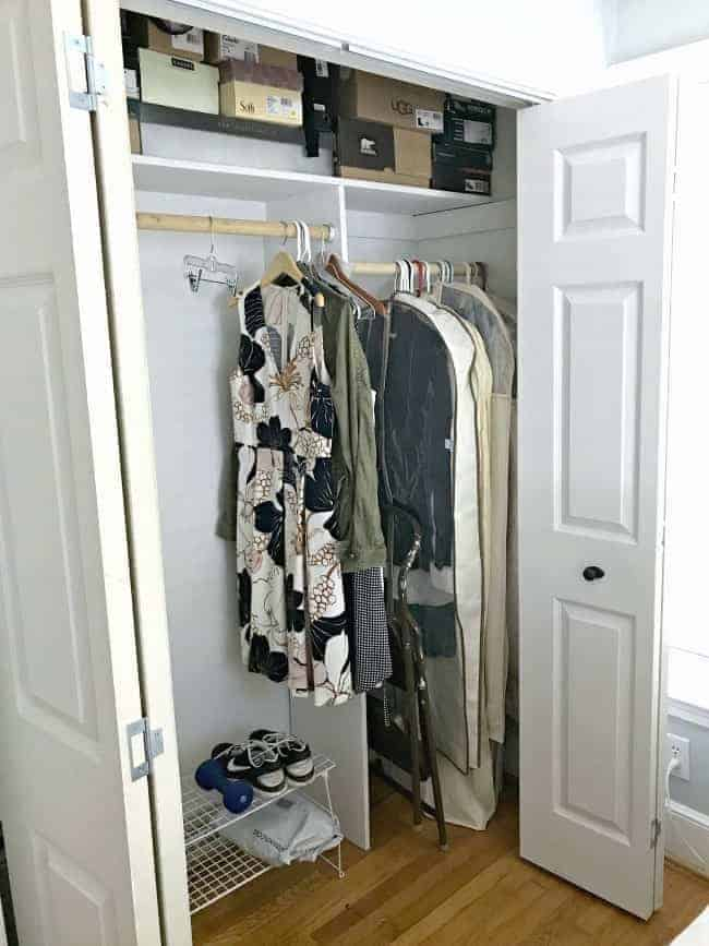 bedroom closet with clothes hanging inside and shoe boxes on the shelf
