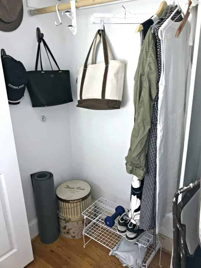 corner of bedroom closet with hat boxes and purses hanging