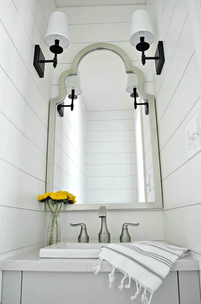 small powder room vanity, mirror and sconces with a striped towel on the vanity and yellow flowers in a glass vase
