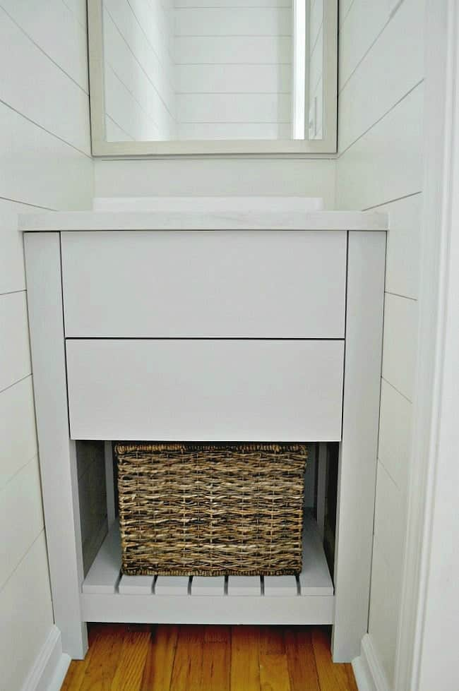 DIY vanity in guest bedroom powder room with basket on bottom shelf