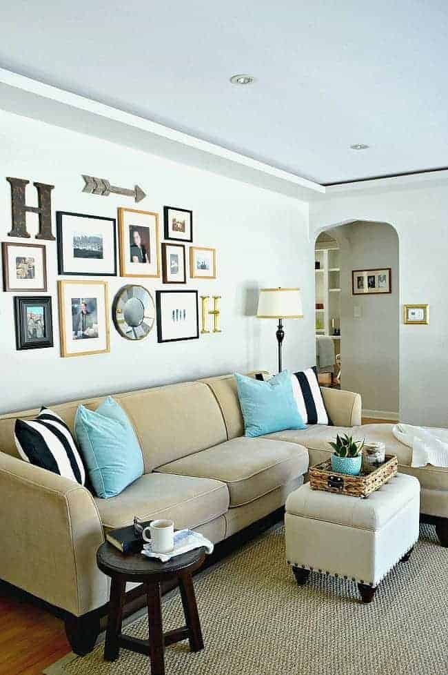 small living room with neutral colored sectional and gallery wall
