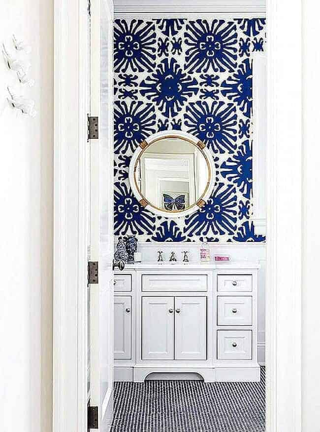 A white bathroom gets a bold punch of color with blue and white wallpaper.