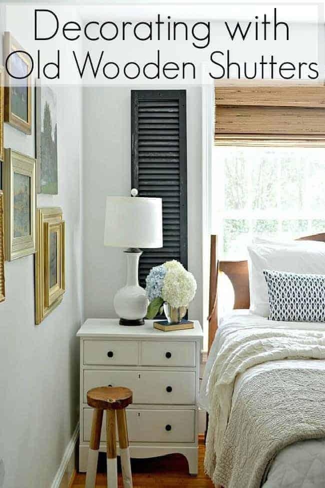 small master bedroom with white nightstand and old wooden shutter on wall next to window