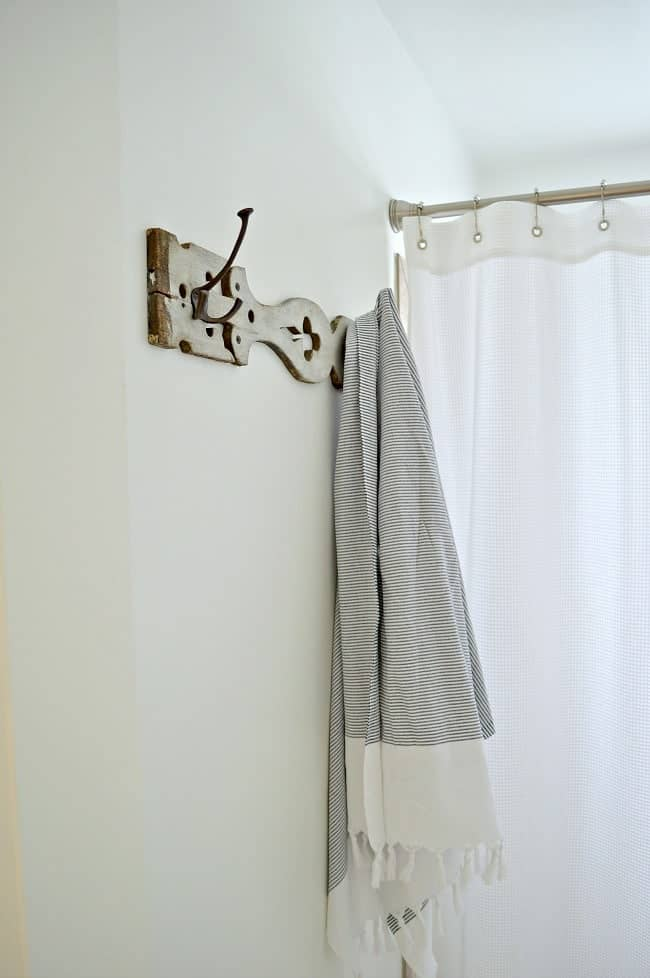 An old porch baluster turned towel holder in a bathroom.