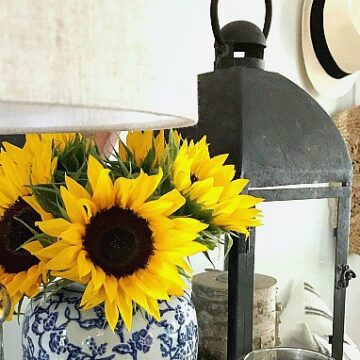 sunflowers in blue and white vase next to a black metal lantern