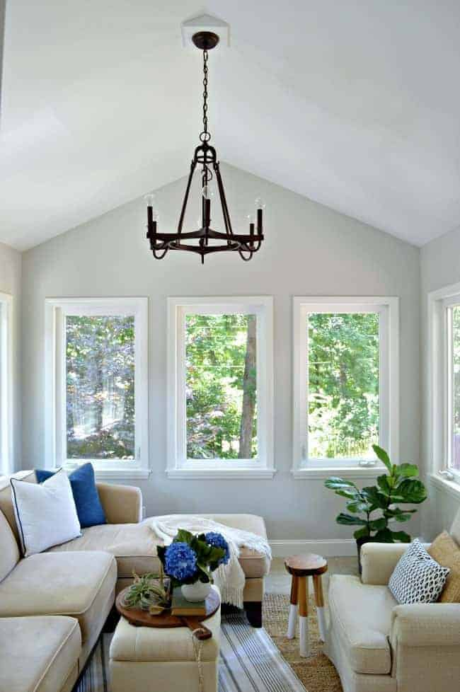 Thrifty ideas for decorating a sunroom using thrifted artwork and paint for a plain white door.