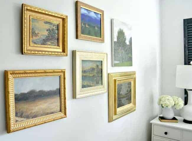 How to use thrift store art to make a gallery wall in a master bedroom. A fun way to repurpose found art from thrift stores and flea markets.
