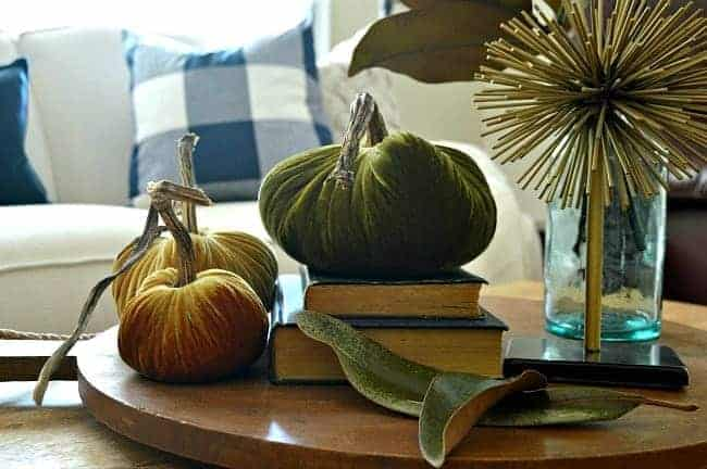 Create a fall display with fresh leaves and velvet pumpkins.