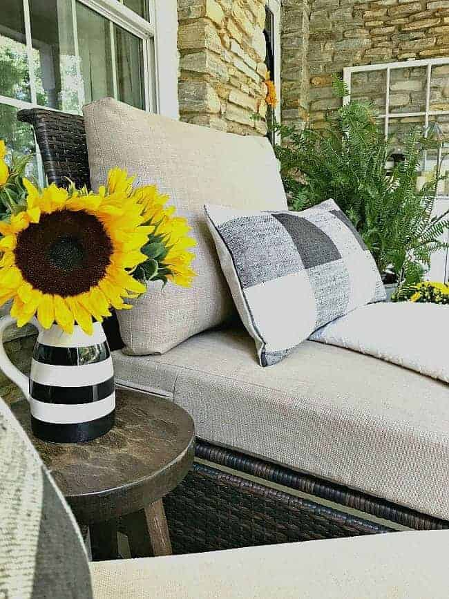 5 tips and decorating ideas for creating a welcoming fall porch for your guests from adding fall color with fresh sunflowers to a cozy seating area.