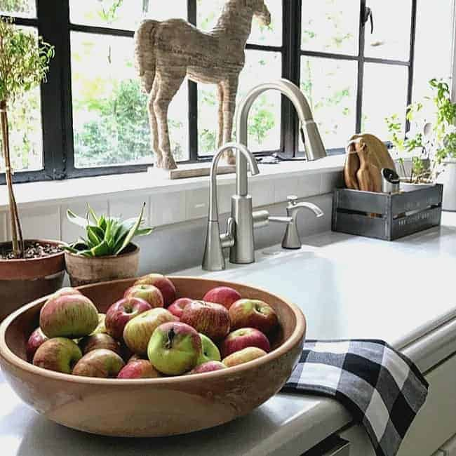 Decorating the kitchen for fall with buffalo check as well as natural elements like apples and plants.