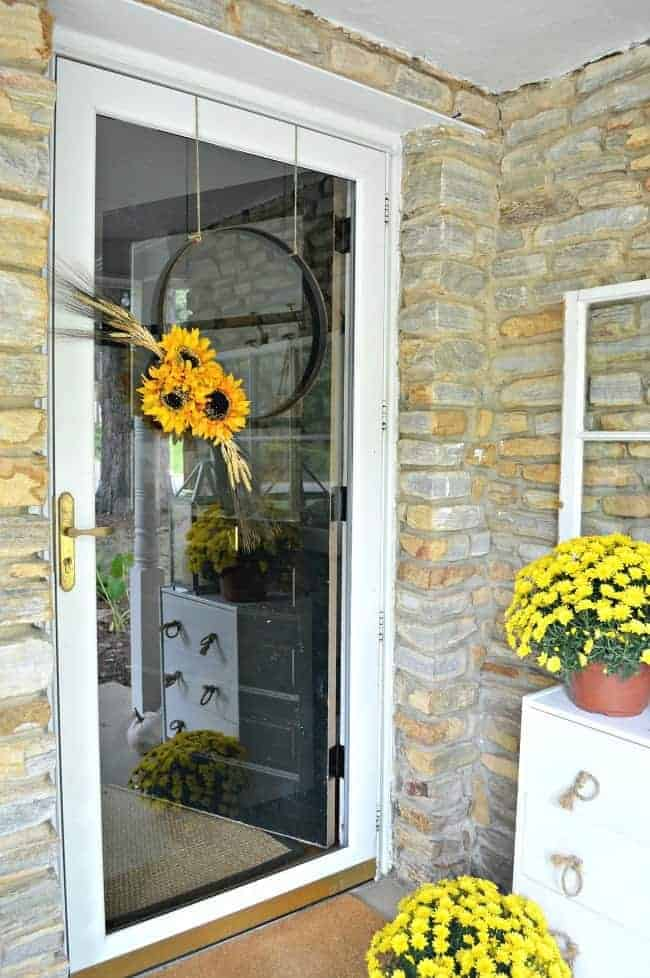 5 tips and decorating ideas for creating a welcoming fall porch for your guests from adding fall color with yellow mums to a simple front door wreath.