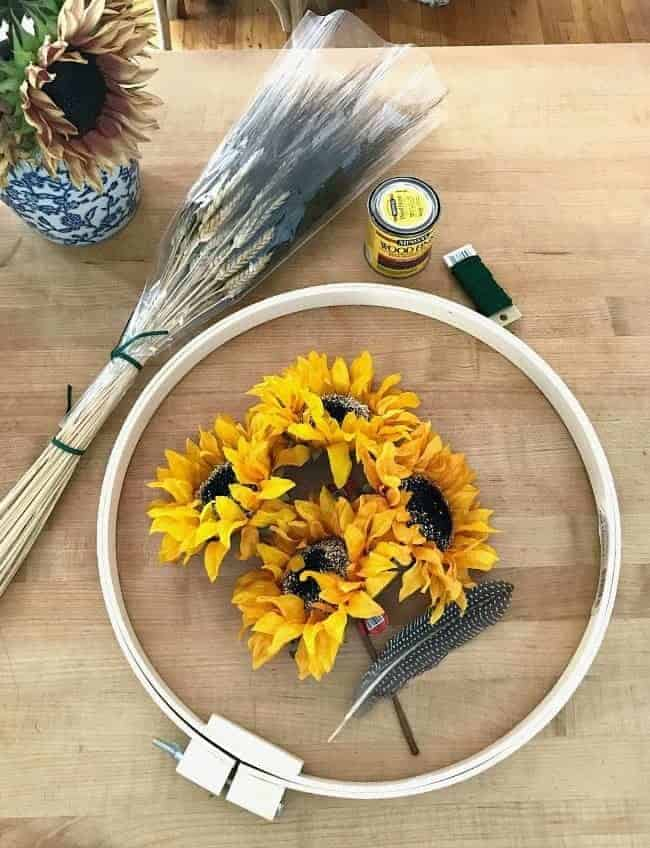 Create a simple DIY fall front door wreath with an embroidery hoop, wheat and faux flowers.