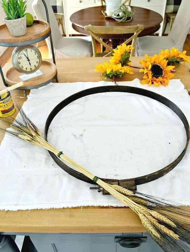 Adding tied wheat to an embroidery hoop to create a simple DIY fall front door wreath.
