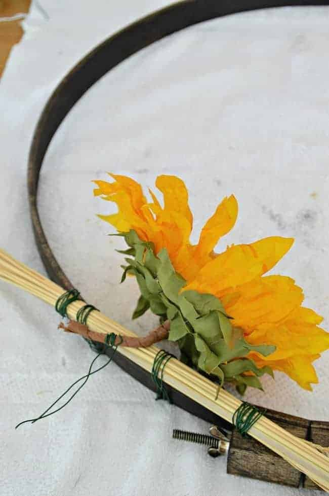 Attaching sunflowers to an embroidery hoop with floral wire to create a simple DIY fall front door wreath.